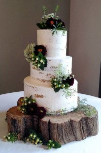 Barely iced wedding cake with fresh flowers.