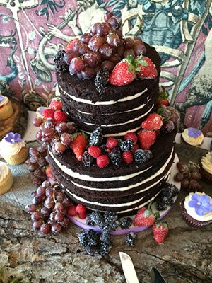 Naked or Barely Iced wedding cake with fruit.